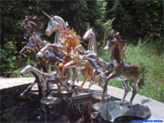 Photo installation of unicorns and horses in the garden.
